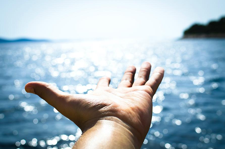 Hand zeigt auf glitzerndes Wasser